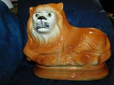 ANTIQUE LEFT FACING STAFFORDSHIRE ? GLAZED RECUMBENT LION WITH GLASS EYES